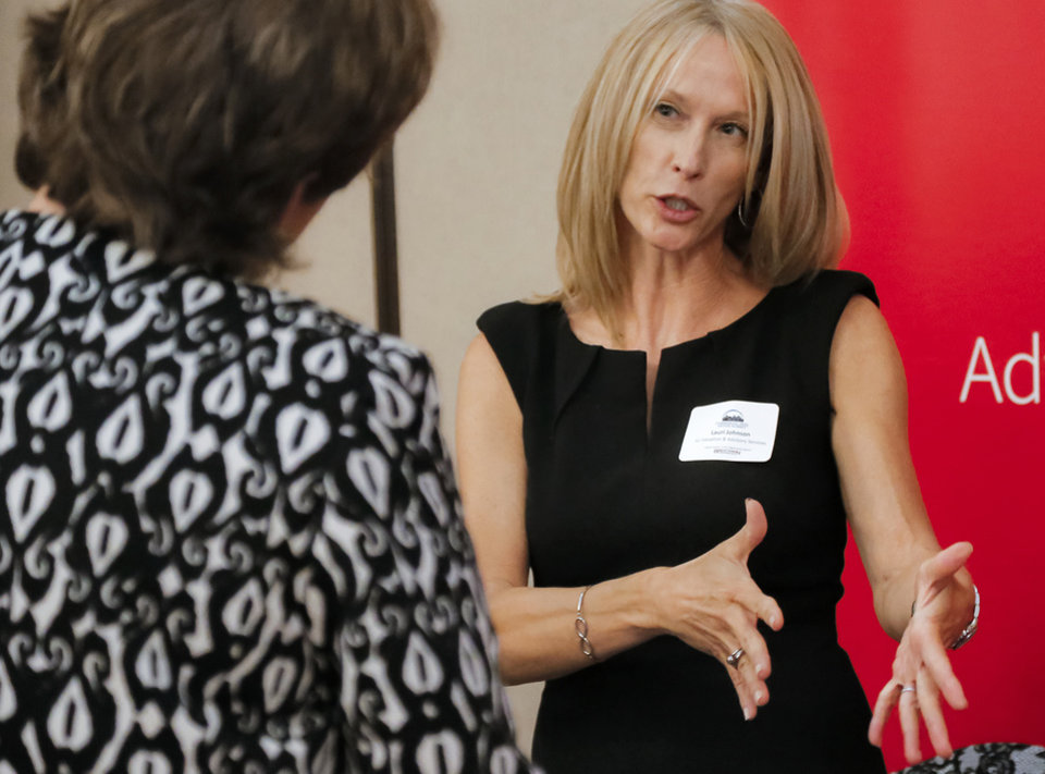 Photo -  Lauri Johnson of JLL Valuations & Advisory Services talks to an attendee of the Commercial Real Estate Summit at a booth in the Nigh University Center at the University of Central Oklahoma Thursday. [PHOTO BY CHRIS LANDSBERGER, THE OKLAHOMAN]