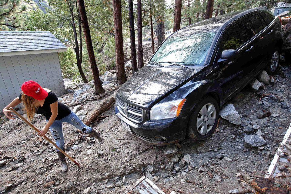 Photo - Jessica Gosney digs out her car after rocks and mud inundated her home in the mountain community of Forest Falls in the San Bernardino Mountains Monday, Aug. 4, 2014. Crews cleared roads in an area where some 2,500 had been stranded after thunderstorms caused mountain mudslides in Southern California over the weekend, while authorities estimated that between 6 and 8 homes were badly damaged and likely uninhabitable. One person was found dead in a vehicle that was caught in a flash flood. A group of campers spent the night at a community center near Forest Falls headed. (AP Photo/Nick Ut)