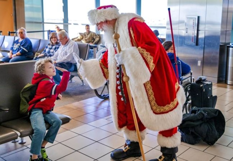 Photo -  Santa Claus gives a high five to Devlin Gonzalez, 8, of Altus, during his holiday travels Thursday at Will Rogers World Airport in Oklahoma City. [Chris Landsberger/The Oklahoman]
