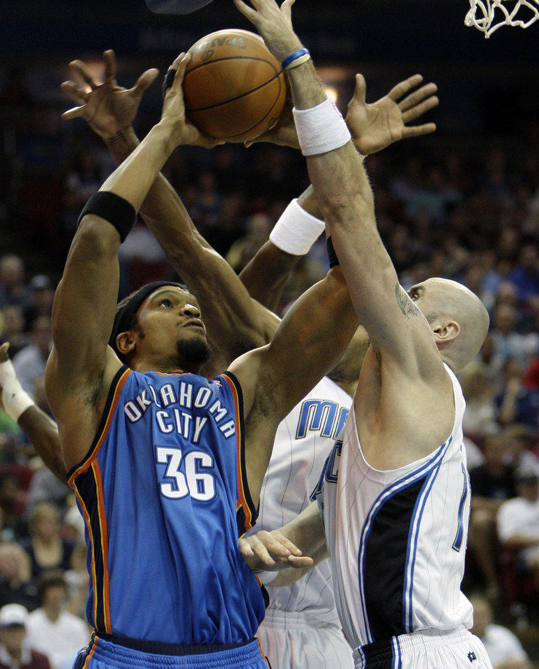 Oklahoma City Thunder center Etan Thomas (36) goes up for a shot against Orlando Magic center Marcin Gortat, of Poland, during the first half of an NBA basketball game in Orlando, Fla., Wednesday, Nov. 18, 2009. (AP Photo/John Raoux) ORG XMIT: DOA102
