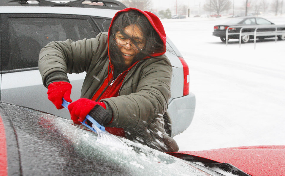 Leslie Florez scrapes her windshield Thursday at Target, NW Expressway and Rockwell.  Photo by Paul B. Southerland, The Oklahoman