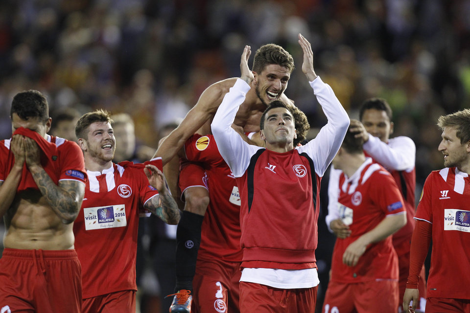 Photo - Sevilla's Reyes, center, and Daniel Carrico from Portugal celebrates on the end their Europa League semifinal second leg soccer match against Valencia at the Mestalla stadium in Valencia, Spain, Thursday, May 1, 2014. Valencia lost 2-0 in the first leg at Sevilla. The game ended 3-1 and Sevilla qualified for the final Europa League. (AP Photo/Alberto Saiz)