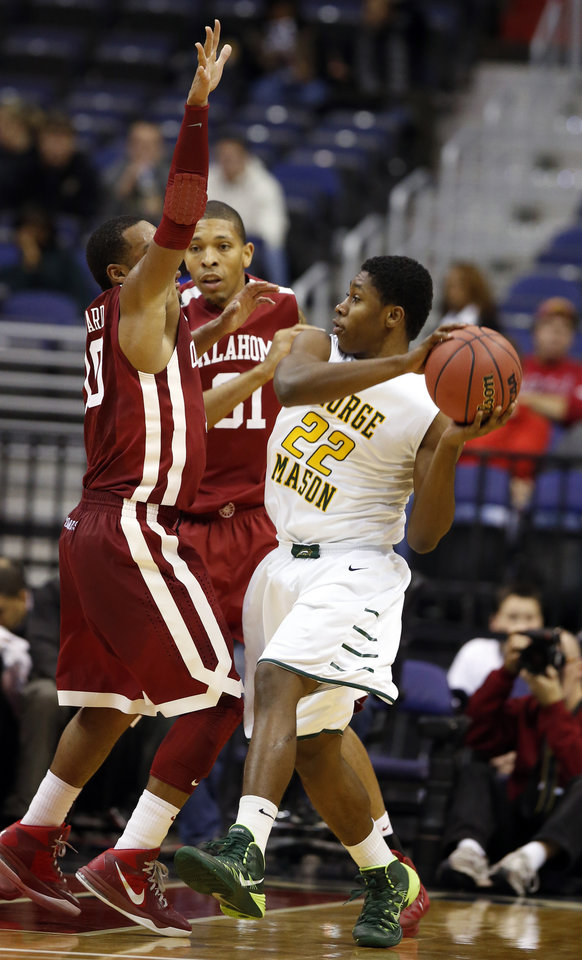 Photo - George Mason guard Marquise Moore (22) looks to pass as he is guarded by Oklahoma guard Jordan Woodard (10) and forward D.J. Bennett (31) during the first half of an NCAA college basketball game in the BB&T Classic, Sunday, Dec. 8, 2013, in Washington. (AP Photo/Alex Brandon)