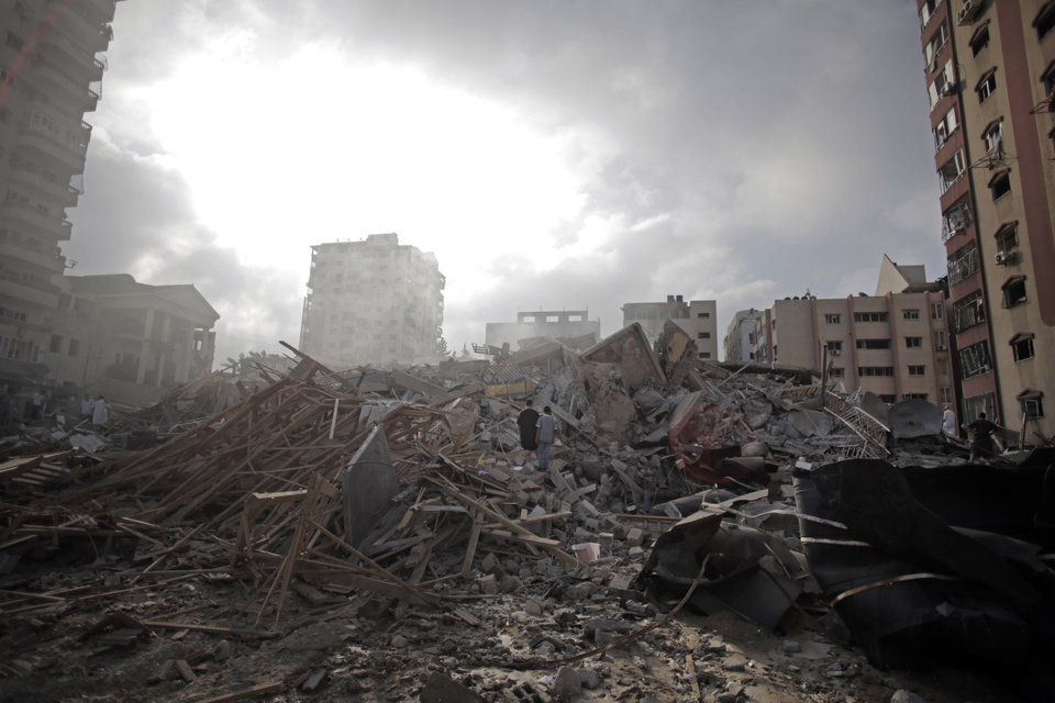 Photo - Palestinians inspect the rubble of the Al-Zafer apartment tower following Israeli airstrikes Saturday that collapsed the 12-story building, in Gaza City, Sunday, Aug. 24, 2014. The Israeli army said the Gaza City apartment tower was targeted because a Hamas command center operated from there. The weekend strikes by Israel marked the first time large buildings were toppled signaling a new escalation in seven weeks of fighting with Hamas. (AP Photo/Khalil Hamra)