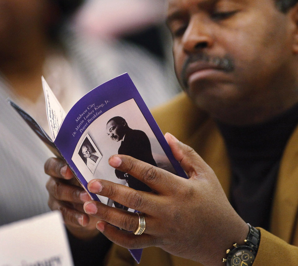Photo - A man flips through the souvenir program while attending the 16th annual Midwest City Dr. Martin Luther King, Jr. Prayer Breakfast inside the Reed Conference Center Monday morning, Jan. 21, 2013. The theme of this year's event is
