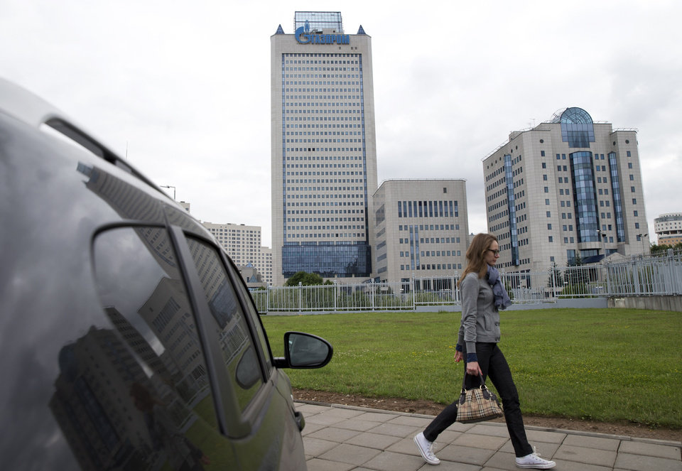 Photo - A woman walks past the headquarters of Russia's state-run natural gas giant Gazprom in Moscow, Russia, Monday, June 16, 2014. Russia said on Monday it would cut off gas supplies to Ukraine as a payment deadline passed and negotiators failed to reach a deal on gas prices. Gazprom spokesman Sergei Kupriyanov said Moscow had no legal grounds to supply Ukraine with any more gas because Ukraine had not paid its bills. (AP Photo/Pavel Golovkin)
