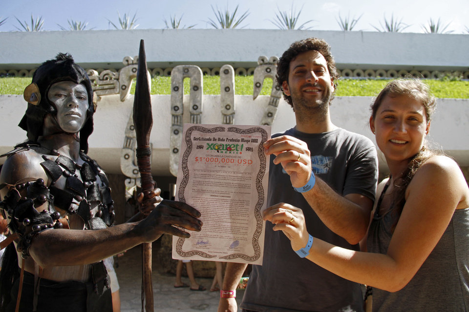 Photo - A man dressed as a Mayan warrior delivers a life certificate for one million dollars, to be paid in case the world comes to an end to an unidentified couple, as they pose for a photo at the Xcaret theme park in Playa del Carmen, Mexico, Saturday, Dec. 15, 2012.  Amid a worldwide frenzy of advertisers and new-agers preparing for a Maya apocalypse, one group is approaching Dec. 21 with calm and equanimity calm: the people whose ancestors supposedly made the prediction in the first place. Mexico's 800,000 Mayas are not the sinister, secretive, apocalypse-obsessed race they've been made out to be.  (AP Photo/Israel Leal)