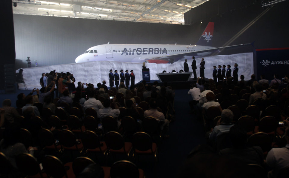 """Photo - The first Airbus A319-100 aircraft in Air Serbia livery is parked in a hangar during the inauguration ceremony at  Belgrade's Nikola Tesla Airport, Serbia, Friday, Oct. 25, 2013. Officials say that Air Serbia, Balkan country's new national carrier partly owned by Etihad Airways, formally starts flying this weekend, spelling the end for the old loss-making JAT Airways. Air Serbia's chief manager Dane Kondic said Friday that the company's inaugural flight will take place on Saturday to Abu Dhabi, United Arab Emirates. He says that """"it is an important flight that will mark a crossroads."""" Kondic and Serbia's deputy prime minister Aleksandar Vucic unveiled at a ceremony at Belgrade's airport an Airbus A319 plane bearing a double-headed eagle logo in Serbia's national, red, white and blue colors. Vucic says Air Serbia hopes to become the leading regional airline. (AP Photo/Darko Vojinovic)"""
