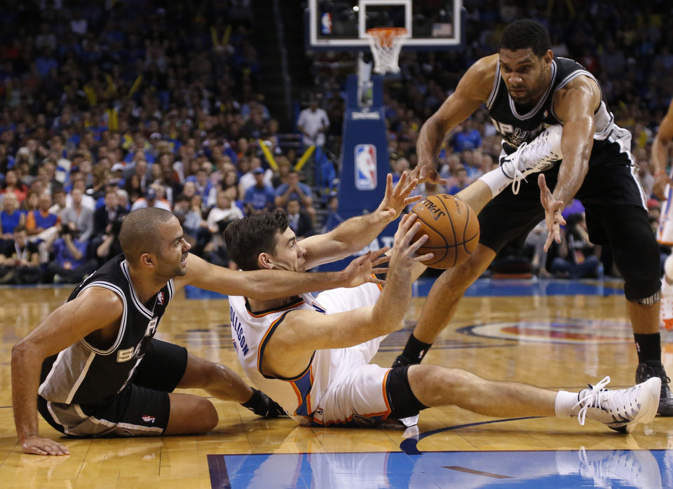 Photo - Oklahoma City Thunder forward Nick Collison (4) passes from between San Antonio Spurs guard Tony Parker, left, and forward Tim Duncan during the third quarter of an NBA basketball game in Oklahoma City, Thursday, April 3, 2014. Oklahoma City won 106-94. (AP Photo/Sue Ogrocki)