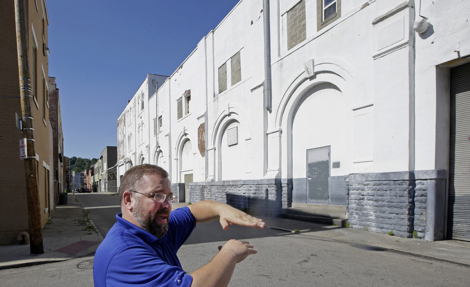 Photo - Steve Hampton, a local architect and the part-time executive director of the nonprofit Brewery District Community Urban Development Corp., stands outside the new Christian Moerlein Brewing Company, right, that is one of three companies now brewing beer in the district, Wednesday, June 19, 2013, in Cincinnati. In the late 19th century, the district was at its peak, with 18 large breweries in operation. (AP Photo/Al Behrman)