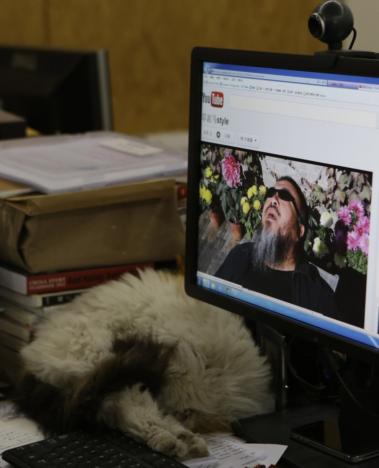 Chinese dissident artist Ai Weiwei appears on a YouTube video clip displayed on a computer screen at his studio in Beijing, China, Thursday, Oct. 25, 2012. In the video, Ai sports a neon-pink T-shirt, black jacket and dark sunglasses and energetically mimics rodeo-style dance moves made famous by South Korean rapper PSY whose original video became an Internet sensation. (AP Photo/Ng Han Guan)