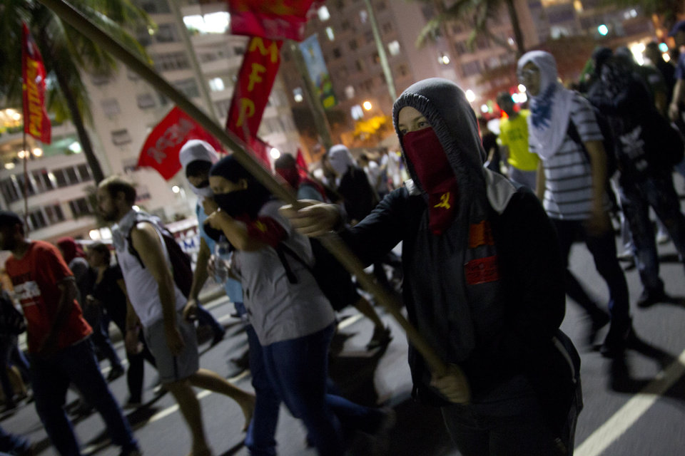 Photo - Demonstrators protest during a march against the FIFA 2014 soccer World Cup at Copacabana beach, Rio de Janeiro, Brazil, Thursday, June 12, 2014. The demonstrators are demanding better public services and protesting the money spent on the soccer tournament. (AP Photo/Leonardo Wen)