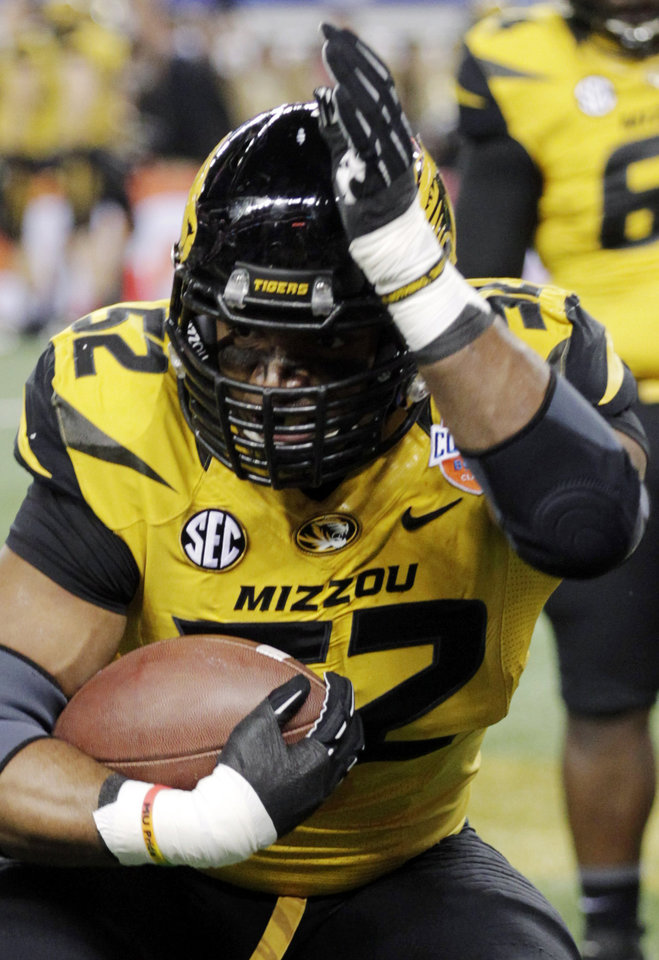 Photo - In this Jan. 3, 2014 photo, Missouri defensive lineman Michael Sam (52) warms up, as he wears an