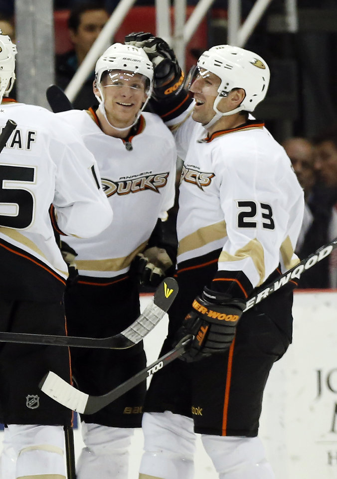 Anaheim Ducks right wing Corey Perry (10) is congratulated by defenseman Francois Beauchemin (23) after scoring a goal in the second period of an NHL hockey game against the Detroit Red Wings, Friday, Feb. 15, 2013, in Detroit. (AP Photo/Duane Burleson)