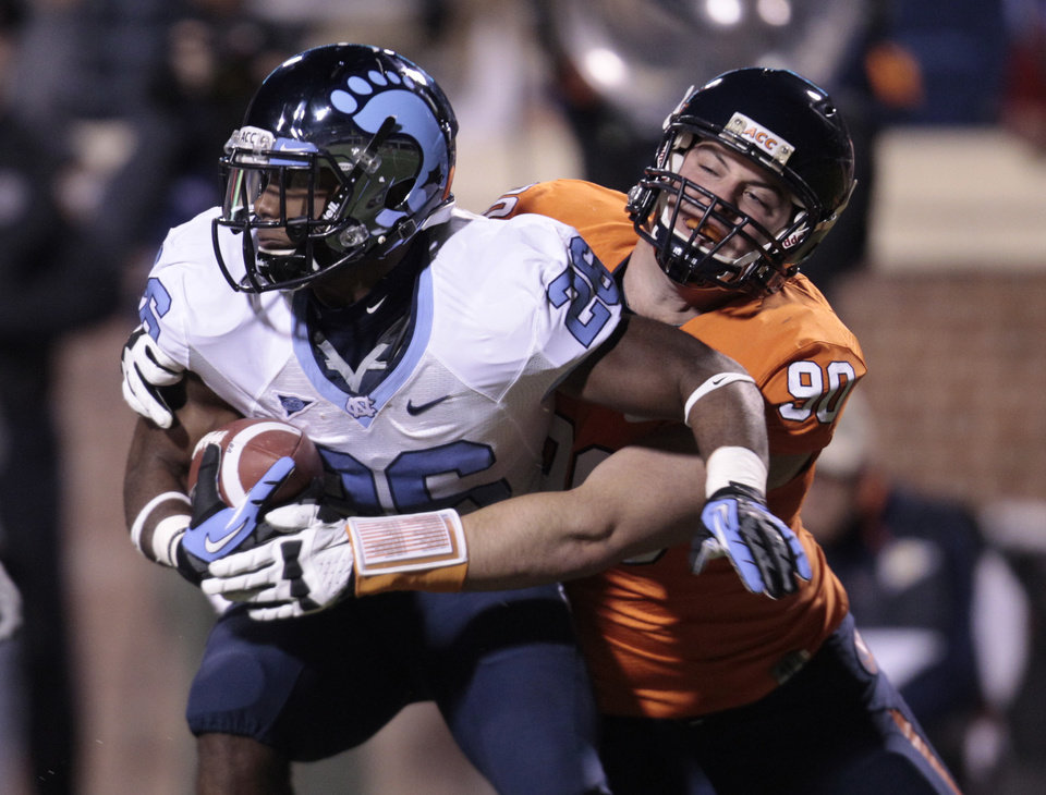 Photo -   North Carolina running back Giovani Bernard (26) is tackled by Virginia defensive end Jake Snyder (90) during the first half of an NCAA college football game at Scott stadium Thursday, Nov. 15, 2012 in Charlottesville, VA (AP Photo/Steve Helber)