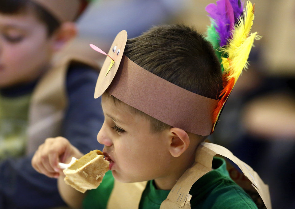 Marc Linn nibbles on his slice of pumpkin pie. Kindergarten students at Eugene Field Elementary School in Oklahoma City have been learning about Thanksgiving traditions and  the history of the national  holiday in America.  Their teachers helped them make paper sack vests and turkey head pieces to wear.  To celebrate the end of the Thanksgiving lesson and reward the students for working so hard, about 80 students in the four kindergarten classes held a pumpkin pie break in the cafeteria Tuesday afternoon, Nov. 20, 2012. The students dressed in their creative paper sack turkey vests and head dresses.   Photo by Jim Beckel, The Oklahoman
