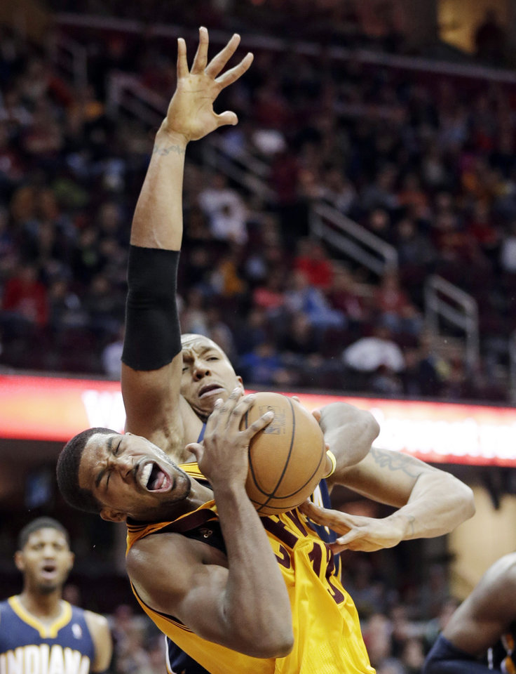 Photo - Cleveland Cavaliers' Tristan Thompson, front, is fouled by Indiana Pacers' David West during the third quarter of an NBA basketball game Sunday, Jan. 5, 2014, in Cleveland. The Pacers won 82-78. (AP Photo/Tony Dejak)