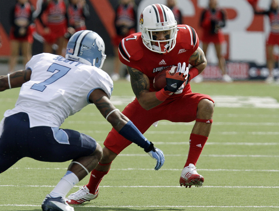 Photo -   Louisville wide receiver Damian Copeland (7) works to avoid North Carolina cornerback Tim Scott, left, after making a pass reception during the first half of an NCAA college football game in Louisville, Ky., Saturday, Sept. 15, 2012. (AP Photo/Garry Jones)