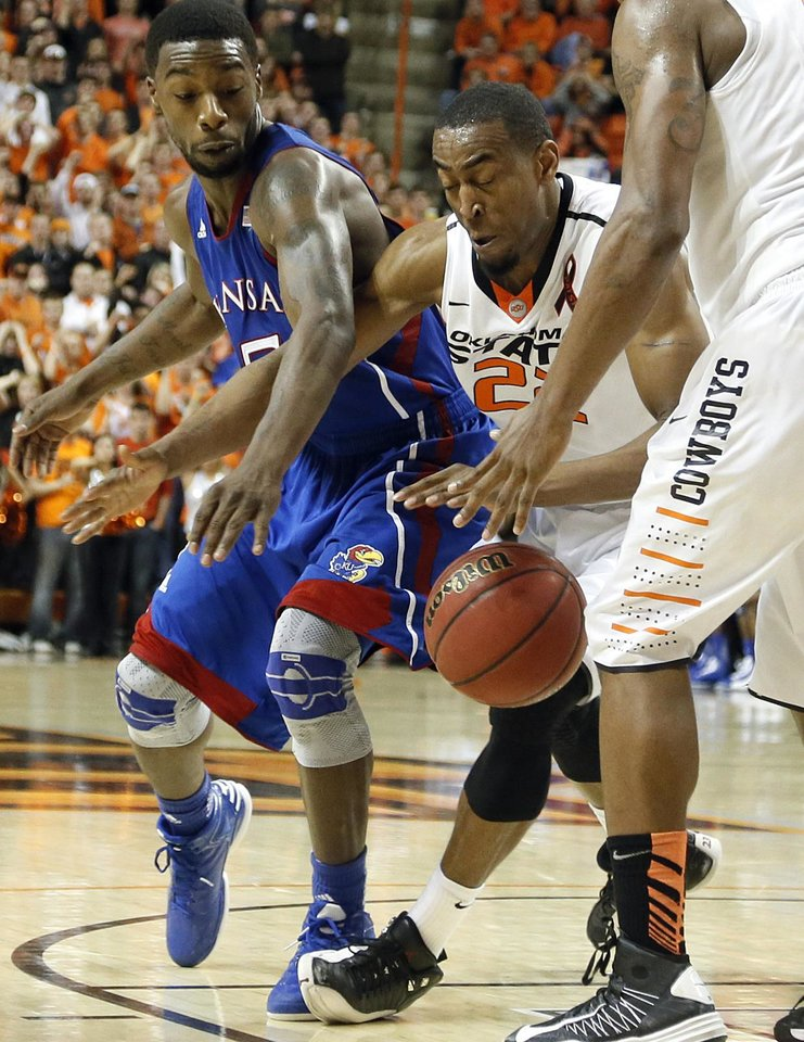 Photo - Kansas' Elijah Johnson (15) and Oklahoma State 's Markel Brown (22) battle for a loose ball during the college basketball game between the Oklahoma State University Cowboys (OSU) and the University of Kanas Jayhawks (KU) at Gallagher-Iba Arena on Wednesday, Feb. 20, 2013, in Stillwater, Okla. Photo by Chris Landsberger, The Oklahoman