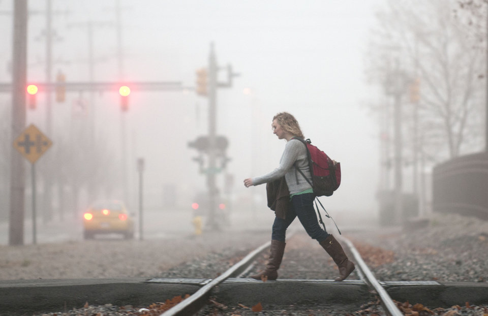 A young woman makes her way toward the Grand Valley State University campus as morning fog changes the landscape in Grand Rapids, Mich., Monday, Dec. 3, 2012. (AP Photo/The Grand Rapids Press, Chris Clark)