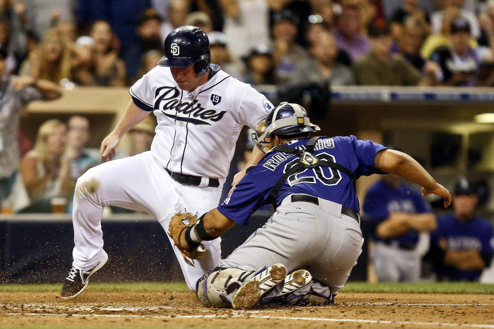 Photo - San Diego Padres' Jedd Gyorko is tagged out by Colorado Rockies catcher Wilin Rosario while trying to score from first on a double by Yasmani Grandal in the fourth inning of a baseball game Monday, Aug. 11, 2014, in San Diego. (AP Photo/Lenny Ignelzi)
