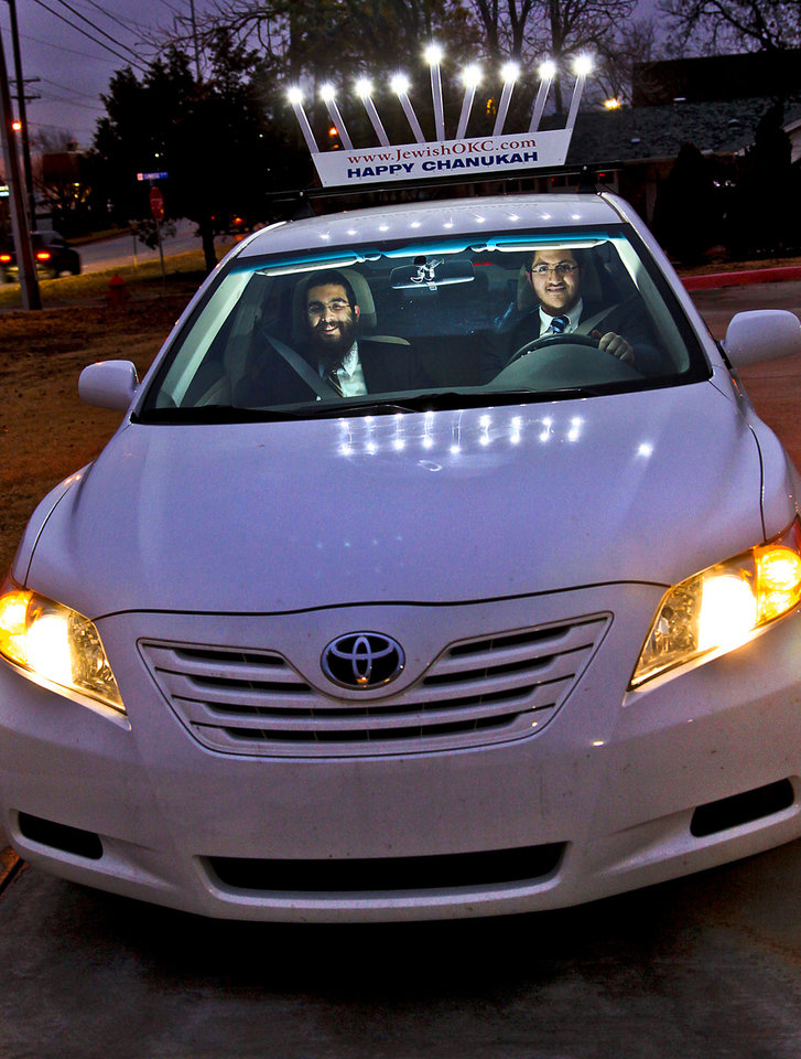 Rabbinical students Zalman Minkowitz, of Canada, and Berel Namdar, of Sweden, from left, pose for a photo in their 'Menorah Car' at the Chabad Jewish Community Center in Oklahoma City, Okla. on Tuesday, Dec. 20, 2011. The two will be driving the car across the state of Oklahoma over the next eight days to spread the word of Hanukkah. Photo by Chris Landsberger, The Oklahoman