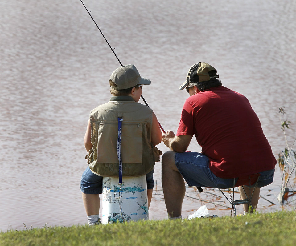 Photo - Chris Wiems and his son, Colton, 6, of Moore, talk while waiting for the next fish to bite on their line. Moore hosted its annual kids fishing derby Saturday morning, July 27, 2013,  at Buck Thomas Park.  As part of the event this year, a charity called the Tackle the Storm Foundation handed out rods and reels to tornado victims. Several bass fishing pros from Oklahoma attended the event to help distribute the fishing equipment and share fishing tips with the young anglers. An event official  said about 250 children participated in the fishing derby. Photo  by Jim Beckel, The Oklahoman.