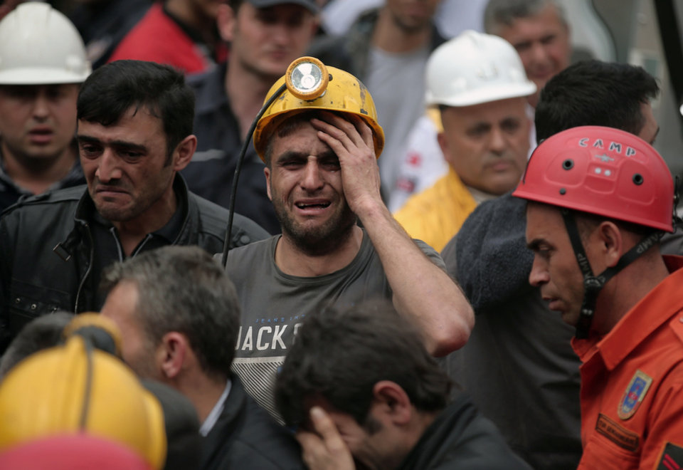 Photo - A miner cries as rescue workers carry the dead body of a miner from the mine in Soma, western Turkey, Wednesday, May 14, 2014. An explosion and fire at the coal mine killed at least 232 workers, authorities said, in one of the worst mining disasters in Turkish history. Turkey's Energy Minister Taner Yildiz said 787 people were inside the coal mine at the time of the accident. (AP Photo/Emrah Gurel)