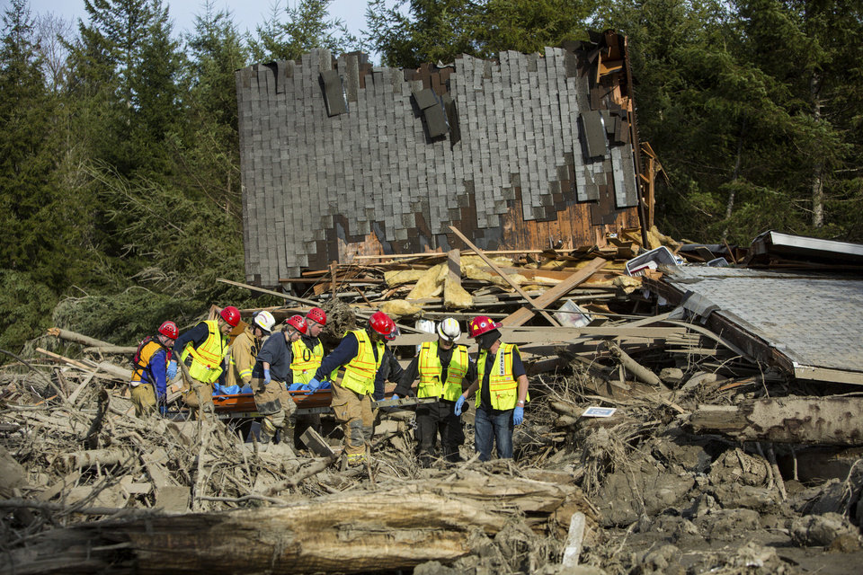 Photo - Rescue workers remove a body from the wreckage of homes destroyed by Saturday's mudslide near Oso, Wash, on Monday, March 24, 2014. The search for survivors of Saturday's deadly mudslide grew Monday to include scores of people who were still unaccounted for as the death toll from the wall of trees, rocks and debris that swept through the rural community rose to at least 14.  (AP Photo/seattlepi.com, Joshua Trujillo)