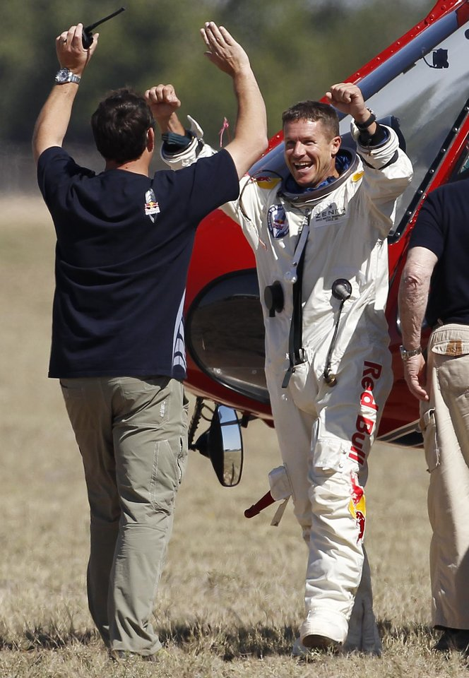 Photo - Felix Baumgartner, right, of Austria, celebrates with Luke Aikins, team skydiving consultant, after Baumgartner successfully jumped from a space capsule lifted by a helium balloon at a height of just over 128,000 feet above the Earth's surface, Sunday, Oct. 14, 2012, in Roswell, N.M.(AP Photo/Ross D. Franklin) ORG XMIT: NMRF123