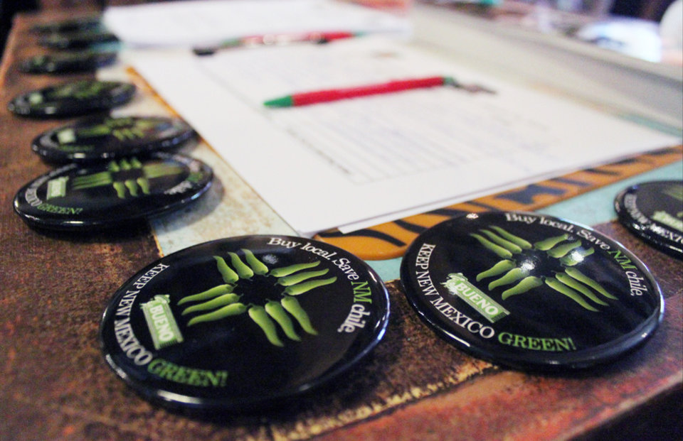 Photo - Officials give out buttons before unveiling a new certification program aimed at protecting the reputation and integrity of New Mexico-grown chile during an event at The Range restaurant in Bernalillo, N.M., on Tuesday, Aug. 19, 2014. The Range is the first restaurant to sign up to participate in the program. (AP Photo/Susan Montoya Bryan)
