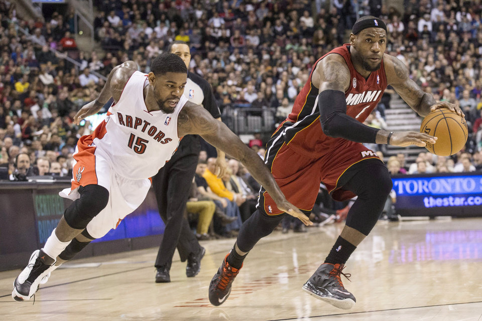 Photo - Miami Heat's LeBron James, right, drives past Amir Johnson during second half NBA basketball action in Toronto on Sunday March 17, 2013. (AP Photo/The Canadian Press, Chris Young)