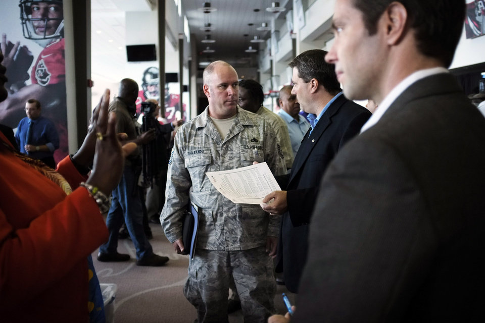 FILE - In this Thursday, Oct. 4, 2012, file photo, United States Air Force Master Sgt. Matt Ditarando, center, talks with Wal-Mart store manager Craig Edwards at the Hiring Our Heroes job fair at Raymond James Stadium in Tampa The number of Americans seeking unemployment aid plummeted last week to seasonally adjusted 339,000, the lowest level in more than four years. The sharp drop offered a hopeful sign that the job market could pick up. (AP Photo/The Tampa Bay Times, Edmund D. Fountain) TAMPA OUT; CITRUS COUNTY OUT; PORT CHARLOTTE OUT; BROOKSVILLE HERNANDO TODAY OUT