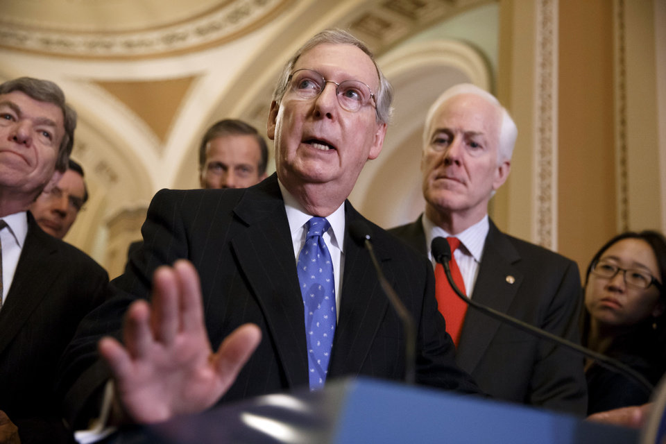 Photo - Senate Minority Leader Mitch McConnell, R-Ky., center, accompanied by fellow GOP lawmakers, speaks to reporters on Capitol Hill in Washington, Tuesday, March 25, 2014, following a GOP caucus lunch. From left are, Sen. Roy Blunt, R-Mo., Sen. John Thune, R-S.D., and McConnell and Senate Minority Whip John Cornyn of Texas. Relenting to GOP objections, Democrats have decided to remove a major roadblock preventing Congress from passing legislation authorizing sanctions on Russia and providing aid to Ukraine.  (AP Photo/J. Scott Applewhite)