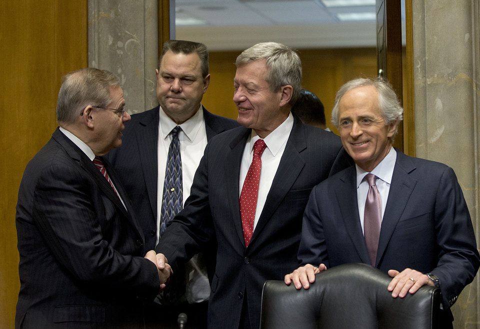 Photo - Retiring Montana Sen. Max Baucus, center, shakes hands with Senate Foreign Committee Chairman Sen. Bob Menendez, D-NJ., accompanied by the committee's ranking Republican Sen. Bob Corker, R-Tenn., right, and Sen. Jon Tester, D-Mont., on Capitol Hill in Washington, Tuesday, Jan. 28, 2014, prior to the start of the committee's hearing on Baucus nomination to become US ambassador to China. The six-term Democratic Senator is expected to sail towards confirmation by his colleagues. If confirmed, Baucus would replace Gary Locke. (AP Photo/Pablo Martinez Monsivais)