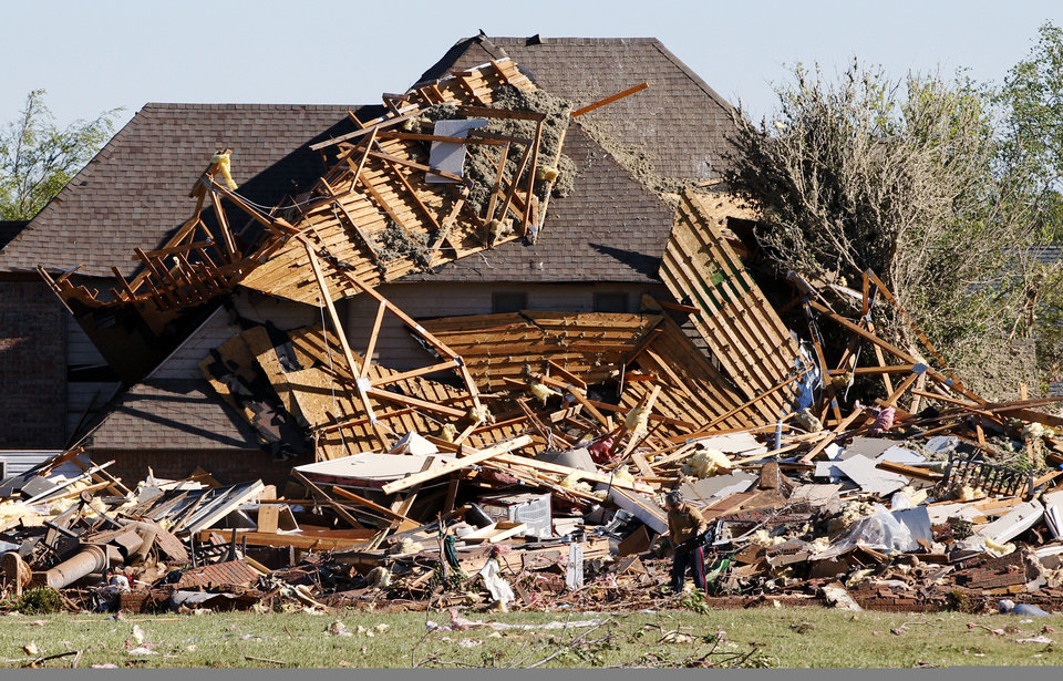 Photo -   Sue Lord is dwarfed by the debris from her home, which is piled up on the neighbor's home, following a tornado in Woodward, Okla., Sunday, April 15, 2012. Lord was in the home when the tornado struck, but was not injured. (AP Photo/Sue Ogrocki)