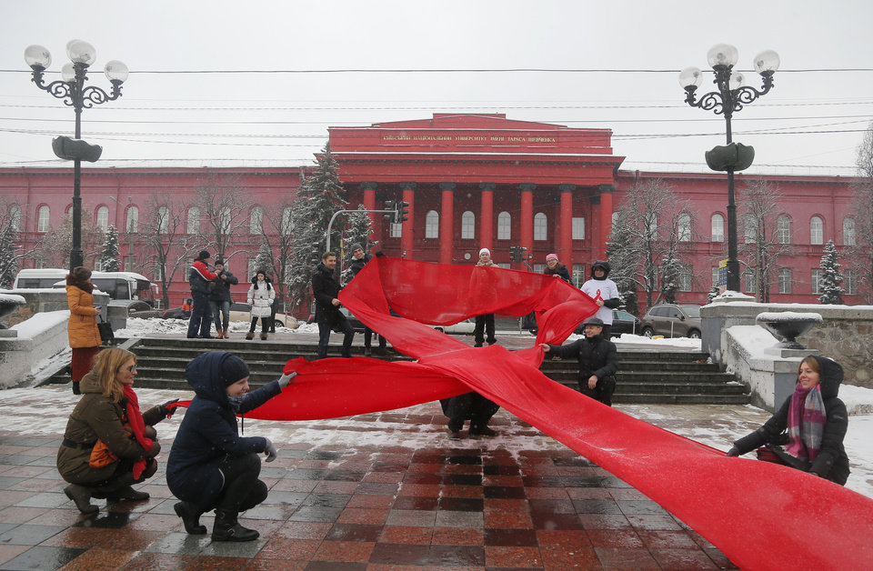 Photo - Activists hold huge red ribbon in front of the Taras Shevchenko National University Kiev, Ukraine,  to mark the 'World AIDS Day' and in memory of those who have died of AIDS Thursday, Dec. 1, 2016. (AP Photo/Efrem Lukatsky)