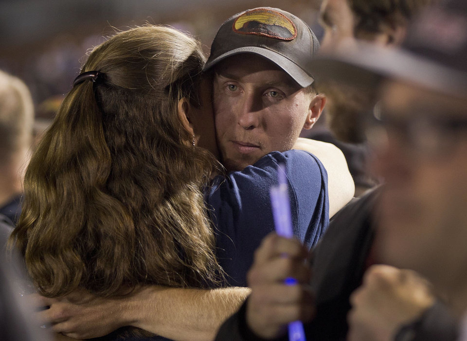 Photo - FILE - In this July 2, 2013 file photo, firefighter Brendan McDonough embraces a mourner near the end of a candlelight vigil in Prescott, Ariz. McDonough was the sole survivor of the 20-man Granite Mountain Hotshot Crew after an out-of-control blaze killed the 19 near Yarnell, Ariz. Investigators are set to release a report Saturday, Sept. 28, 2013, on the deaths of the 19 elite firefighters who became trapped by flames in a brush-choked canyon north of Phoenix.(AP Photo/Julie Jacobson, File)