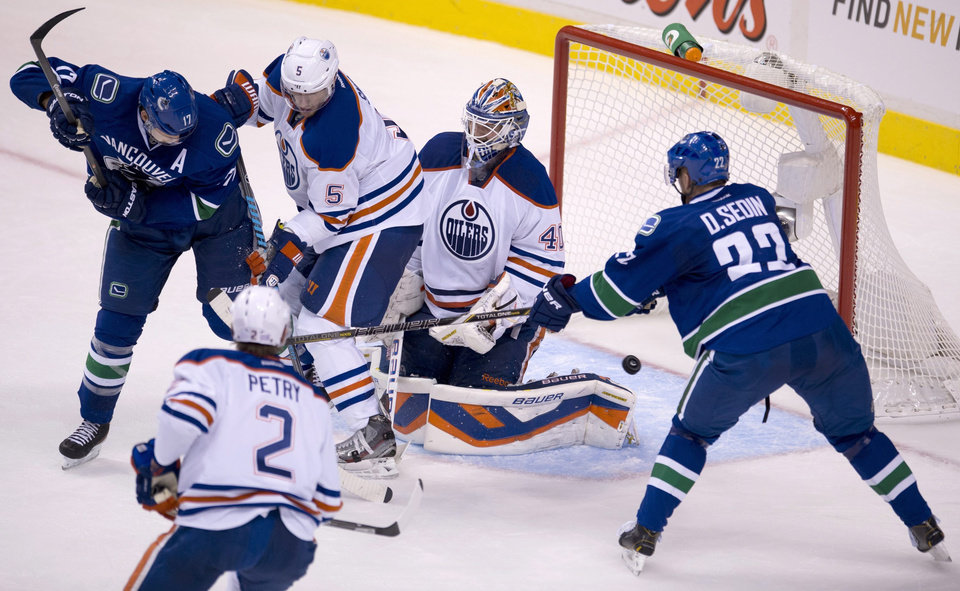Photo - Vancouver Canucks left wing Daniel Sedin (22) puts a shot past Edmonton Oilers goalie Devan Dubnyk (40) as Vancouver Canucks center Ryan Kesler (17), Edmonton Oilers defenseman Jeff Petry (2) and Edmonton Oilers defenseman Ladislav Smid (5) look on during the second period of NHL hockey action in Vancouver, British Columbia, Saturday, Oct. 5, 2013. (AP Photo/The Canadian Press, Jonathan Hayward)