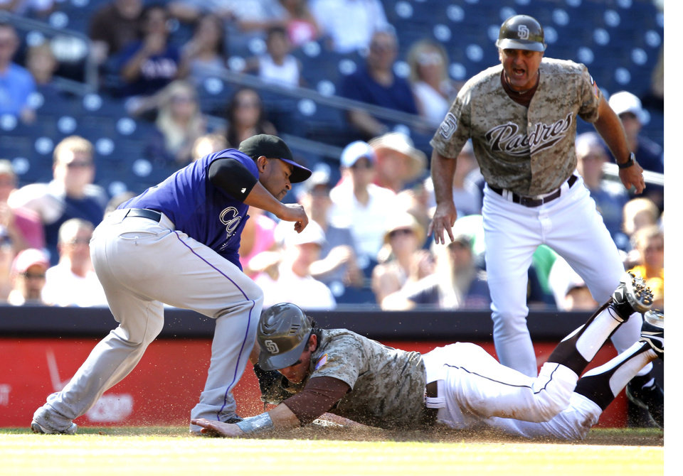 Photo -   San Diego Padres' John Baker, center, beats the tag by Colorado Rockies third baseman Chris Nelson, left, as Padres third base coach Glenn Hoffman looks on during the fifth inning of their baseball game in San Diego, Sunday, Sept. 16, 2012. (AP Photo/Alex Gallardo)