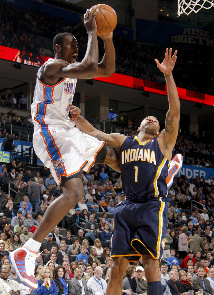 Photo - Oklahoma City's Serge Ibaka (9) passes the ball beside Indiana's Dahntay Jones (1)  during the NBA basketball game between the Oklahoma City Thunder and the Indiana Pacers at the Oklahoma City Arena, Wednesday, March 2, 2011. Photo by Bryan Terry, The Oklahoman