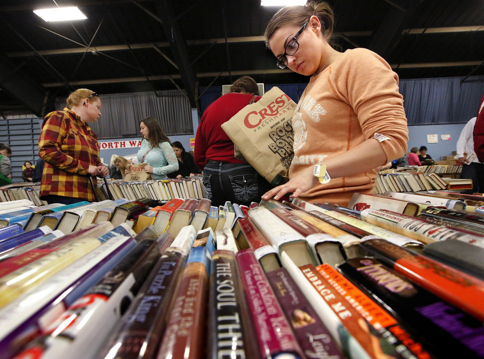 Carrying a paper sack with books she\'s already selected, this woman carefully reads the spines of books spread neatly on a table. Several thousand bibliophiles and bargain hunters crowded into Oklahoma Expo Hall at State Fair Park on Saturday, Feb. 23, 2013, in a quest to find reading material at deeply discounted prices. Friends of the Metropolitan Library System is holding their much-anticipated annual book sale this weekend. The sale continues Sunday from 9 a.m. to 5:30 p.m. Photo by Jim Beckel, The Oklahoman