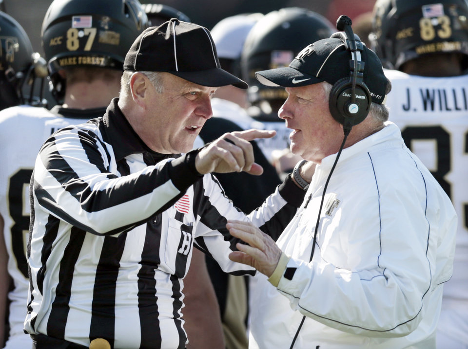 Wake Forest head coach Jim Grobe, right, talks with head linesman John Busch, left, in the first quarter of an NCAA college football game against Vanderbilt on Saturday, Nov. 30, 2013, in Nashville, Tenn. (AP Photo/Mark Humphrey)