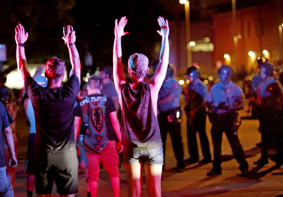 Photo - Protesters hold their hands in the air at the Oklahoma City Police Department during a protest near the intersection of 23rd and Classen in Oklahoma City, Saturday, May 30, 2020. The protest was in response to the death of George Floyd. [Sarah Phipps/The Oklahoman]