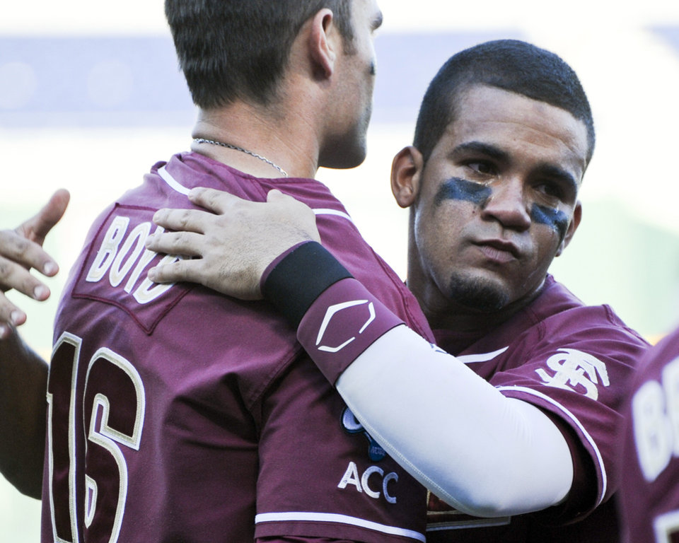 Photo -   A crying Florida State's Devon Travis, right, hugs teammate Jayce Boyd, left, following an NCAA College World Series baseball game against Arizona in Omaha, Neb., Thursday, June 21, 2012. Arizona defeated Florida State 10-3. (AP Photo/Dave Weaver) (AP Photo/Eric Francis)
