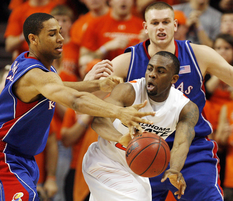 OSU's James Anderson (23) passes the ball away from Xavier Henry (1), left, and Cole Aldrich (45) of KU in the second half during the men's college basketball game between the University of Kansas (KU) and Oklahoma State University (OSU) at Gallagher-Iba Arena in Stillwater, Okla., Saturday, Feb. 27, 2010. OSU won, 85-77. Photo by Nate Billings, The Oklahoman