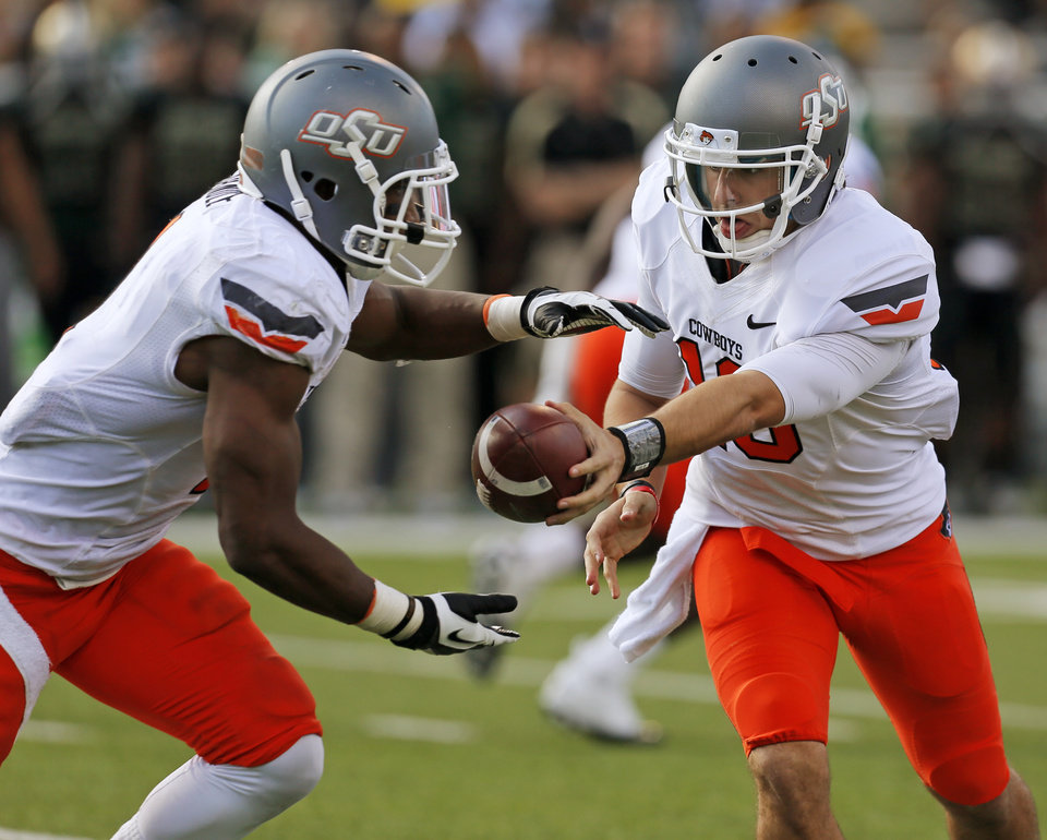Photo - Oklahoma State's Clint Chelf (10) hands the ball to Joseph Randle (1) during a college football game between the Oklahoma State University Cowboys (OSU) and the Baylor University Bears at Floyd Casey Stadium in Waco, Texas, Saturday, Dec. 1, 2012. Photo by Nate Billings, The Oklahoman