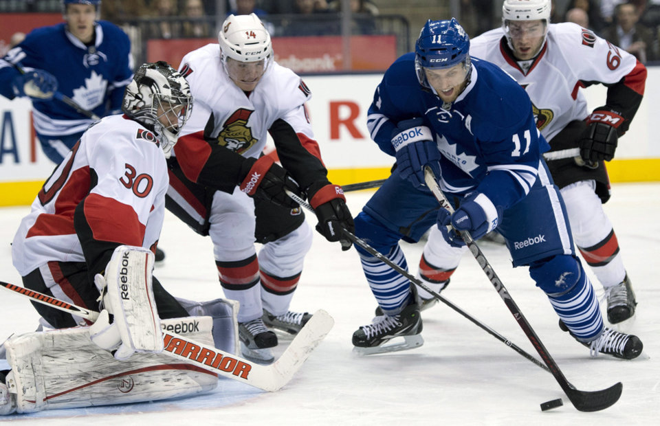 Toronto Maple Leafs center Jay McClement (11) tries to shoot on Ottawa Senators goaltender Ben Bishop (3) as left winger Colin Greening (14) tries to break up the play during the second period of an NHL hockey game in Toronto on Wednesday, March 6, 2013. (AP Photo/The Canadian Press, Frank Gunn)