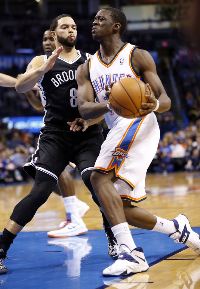 Photo - Thunder's Reggie Jackson (15) tries to get past Brooklyn's Deron Williams in the first half of an NBA basketball game where the Oklahoma City Thunder were defeated 95-93 by the Brooklyn Nets at the Chesapeake Energy Arena in Oklahoma City, on Thursday, Jan. 2, 2014. Photo by Steve Sisney The Oklahoman