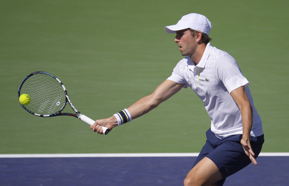 Photo - Julien Benneteau, of France, volleys with Novak Djokovic, of Serbia, in their quarterfinal match at the BNP Paribas Open tennis tournament on Friday, March 14, 2014, in Indian Wells, Calif. (AP Photo/Mark J. Terrill)